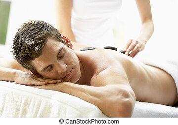 Young Man Enjoying Hot Stone Treatment