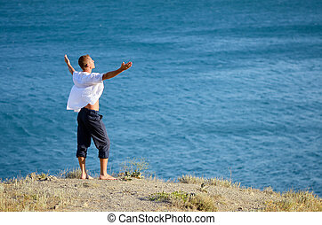 Young man enjoying the sea breeze while standing on a rock