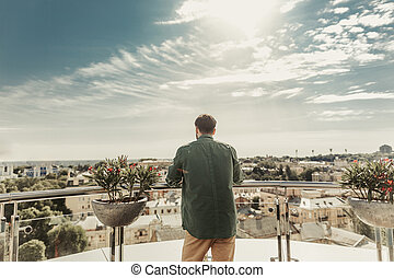 Young man enjoying the view from the balcony