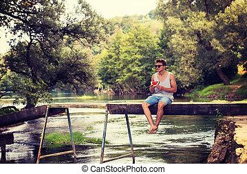 man enjoying watermelon while sitting on the wooden bridge