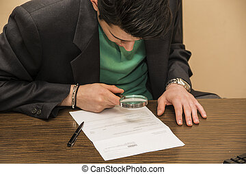 Young Man Examining Contract with Magnifying Glass - Young...