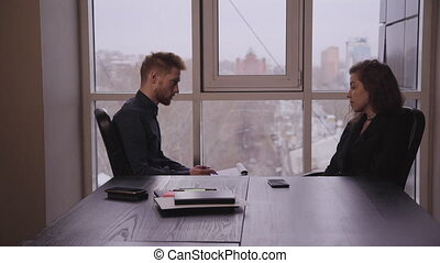 Young man executive interviewing woman sitting at desk on window background in office.