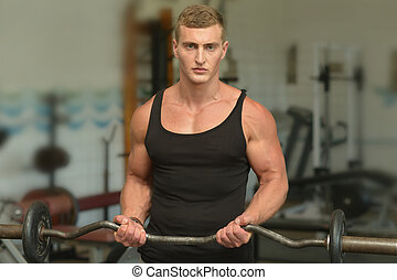 Young man exercises in gym