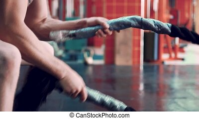 young man exercising arms and shoulders with rope in gym