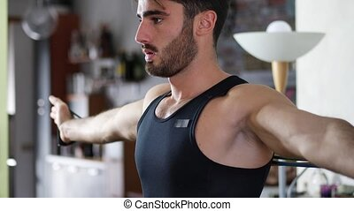 Young man exercising at home with elastic bands - Young man...