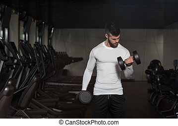 Young Man Exercising Biceps With Dumbbells