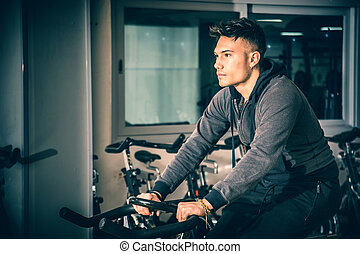 Young man exercising in gym: spinning on stationary bike