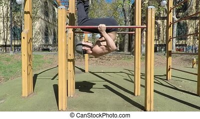 Young man exercising in outdoor gym