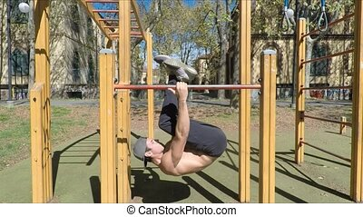 Young man exercising in outdoor gym - Attractive shirtless...