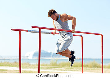 young man exercising on parallel bars outdoors - fitness,...