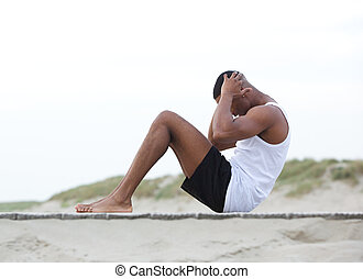 Young man exercising on the beach doing sit ups - Side view ...
