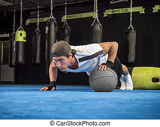 Young man exercising pecs in gym with push-ups