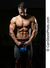 Young Man Exercising With Kettle Bell