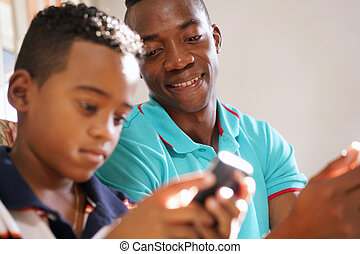 Young Man Explaining Mobile Phone Internet To Boy At Home