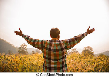 Young man farmer in scott shirt standing arms raised in a field of barley or wheat crops at sunset or sunrise