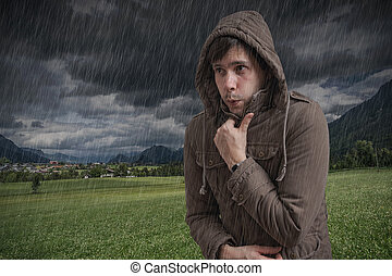 Young man feeling cold during thunderstorm.