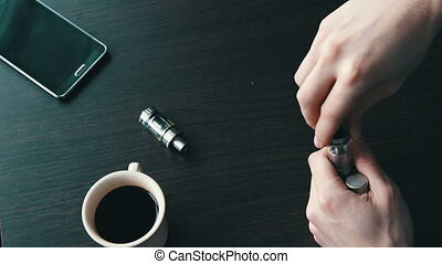 young man fills for liquid smoking electronic cigarette