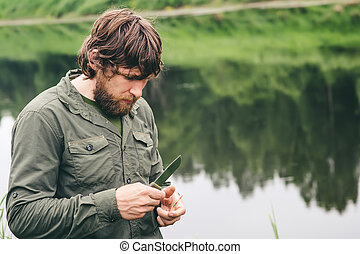 Young Man Fisherman bearded standing with knife and rod...