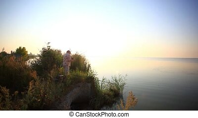 Young man fishing at misty sunrise in the morning