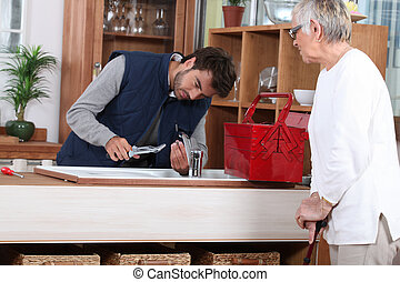 young man fixing faucet older woman