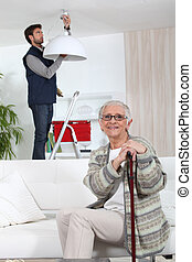 young man fixing lamp for older woman