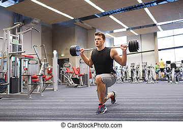 young man flexing muscles with barbell in gym - sport, ...