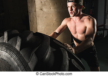 Young man flipping tire at gym