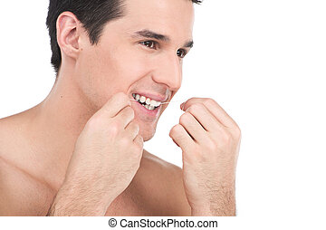 young man flossing his teeth isolated on white background. guy is flossing his teeth in front of bathroom mirror