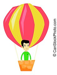 Young man flying in hot air balloon.