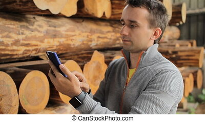 Young man forestry engineer touch phone in front of wood.