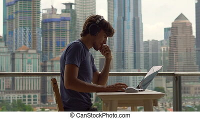 Young man freelancer workes on his laptop at a balcony with...