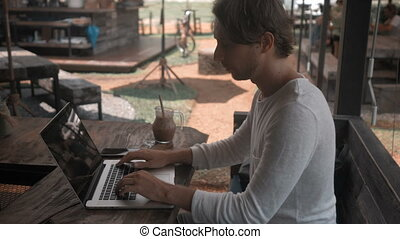 young man freelancer working on a laptop computer in outdoor cafe