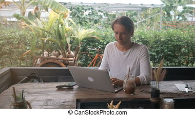 young man freelancer working on a laptop in outdoor cafe