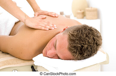 young man getting a massage - young man in a spa getting a...