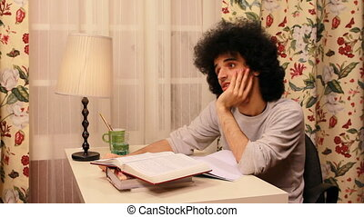young man getting bored while studying