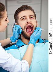 Young man getting his teeth checked by a dentist. - Shot of...
