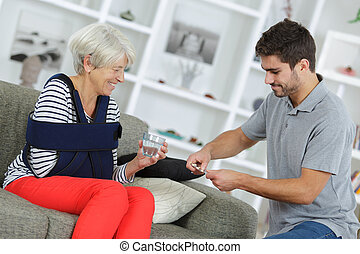 Young man getting tablets for lady with her arm in a sling