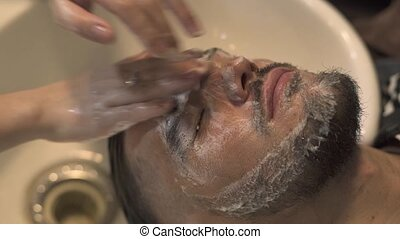 Young man getting wash and face massage in male salon. Close up face massage to bearded man in barber shop. Male skin care concept.
