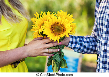 young man gives a bouquet of sunflowers
