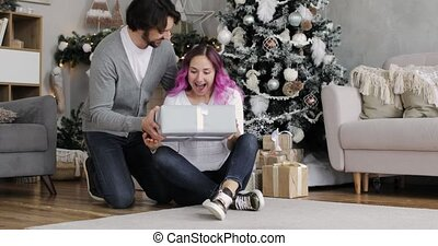 Young man gives a gift to his surprised wife in the New Year's interior at home.