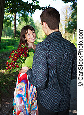 Young man gives a girl a bouquet of red roses in a summer park