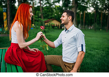 Young man gives flower to woman, romantic meeting