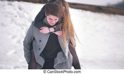 Young man giving a carries on his back his happy girlfriend