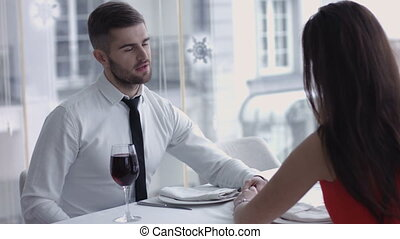 Young man giving a toast and drinking wine together with his adorable lady