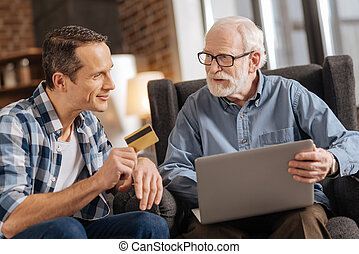 Young man giving bank card to his father using laptop -...