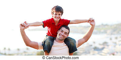 Young man giving child piggyback ride