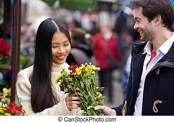 Young man giving flowers to beautiful woman