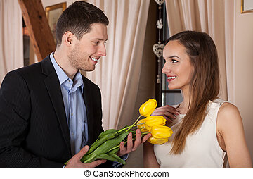 Young man giving flowers
