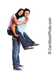 Young man giving girlfriend a piggyback ride