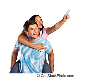 Young man giving girlfriend a piggyback ride on white...
